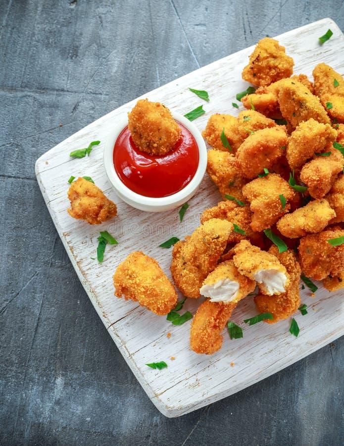 Smażyć crispy kurczak bryłki z ketchupem na białej desce obraz stock
