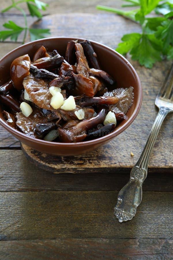 Smażyć dzikie pieczarki z czosnkiem w ceramicznym pucharze obrazy stock