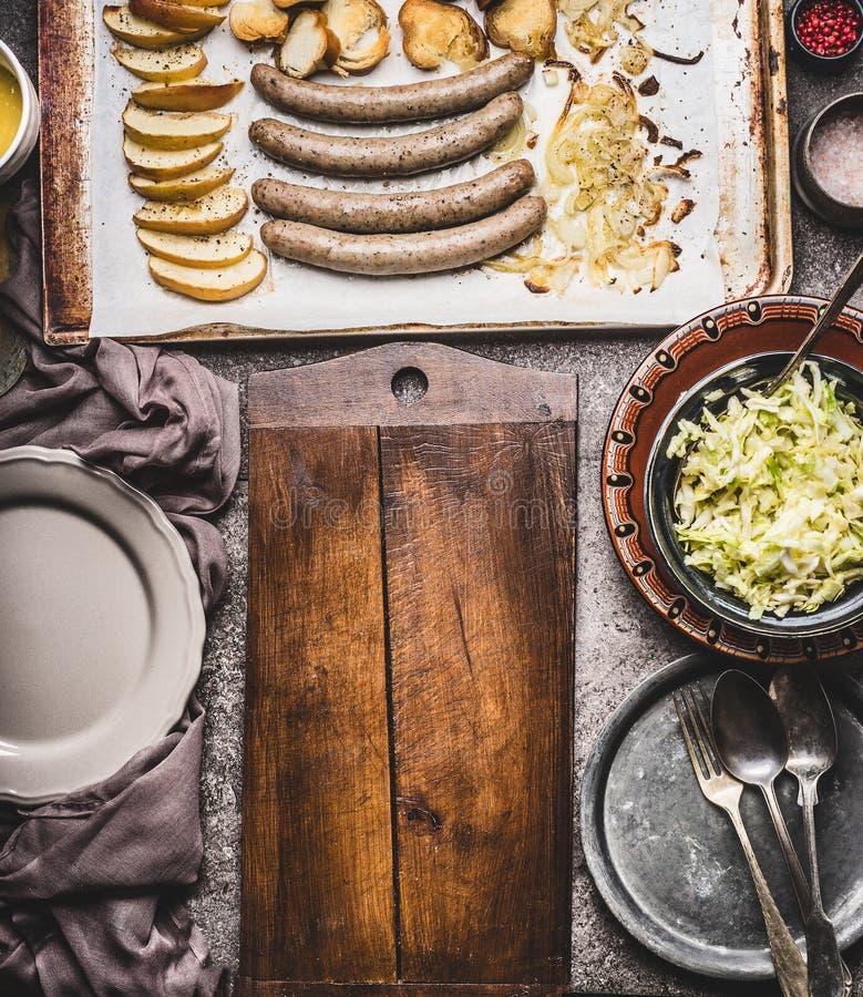 Smażyć kiełbasy na wypiekowej tacy z wypiekowymi jabłkami, cebulami i ług babeczki grzanką z słuzyć na wieśniaka stole z białą co zdjęcia stock