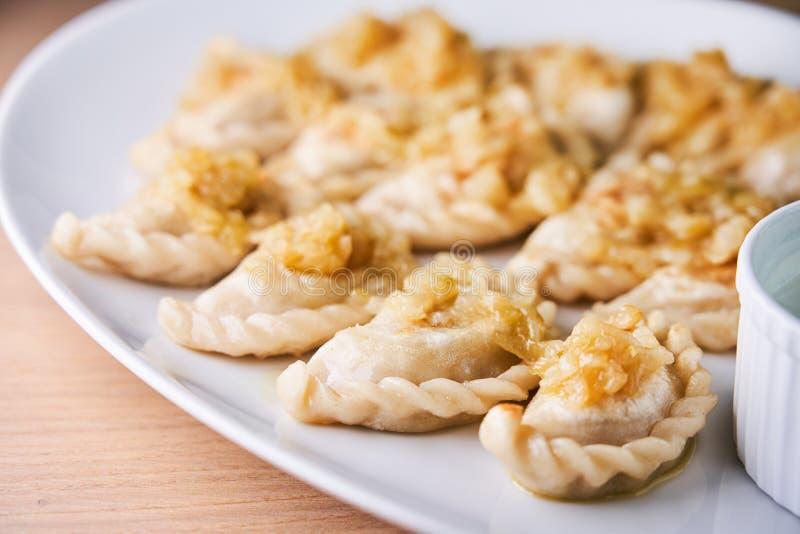Smażyć kluchy faszerować z mięsem carmelized cebuli na bielu talerzu obraz stock