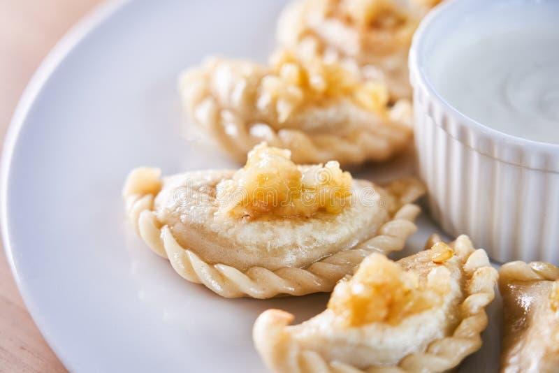 Smażyć kluchy faszerować z mięsem carmelized cebuli na bielu talerzu obrazy royalty free