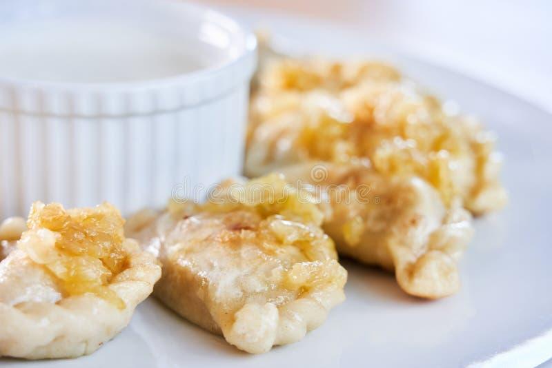 Smażyć kluchy faszerować z mięsem carmelized cebuli na bielu talerzu zdjęcia royalty free