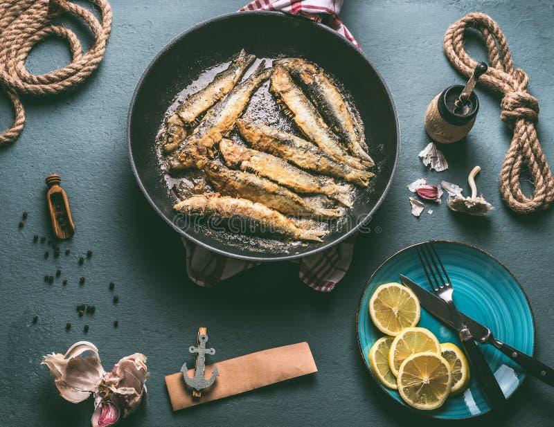 Smażyć sardynki w smażyć nieckę i składniki dla smakowitego owoce morza kucharstwa Kulinarny przygotowanie ryba obraz royalty free