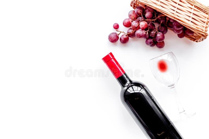 Smaak rode wijn Fles van rode wijn, glas en rode druif op witte hoogste mening als achtergrond copyspace royalty-vrije stock fotografie