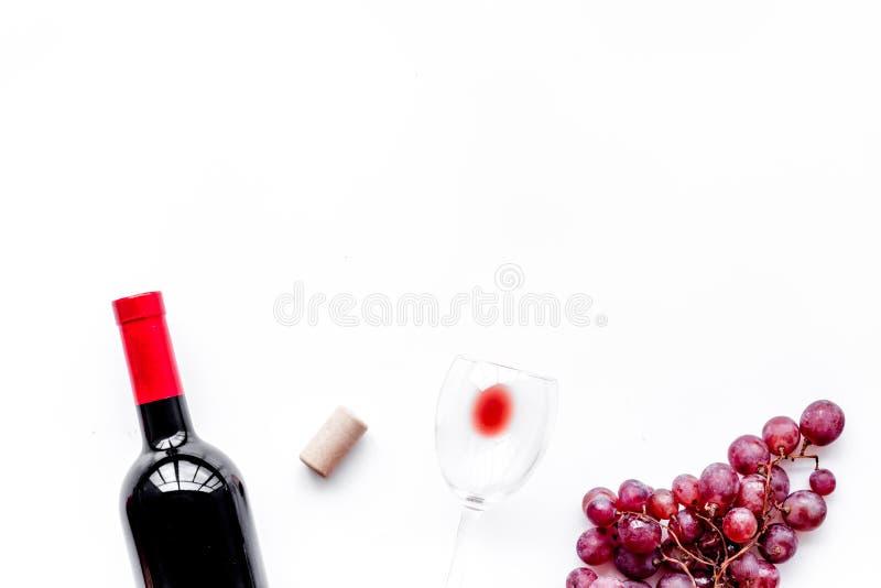 Smaak rode wijn Fles van rode wijn, glas en rode druif op witte hoogste mening als achtergrond copyspace royalty-vrije stock foto