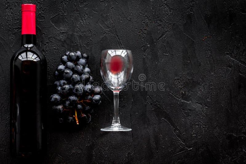 Smaak rode wijn Fles van rode wijn, glas en zwarte druif op zwarte steen hoogste mening als achtergrond copyspace royalty-vrije stock fotografie