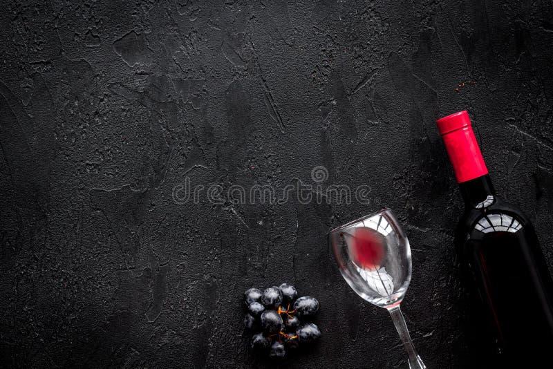 Smaak rode wijn Fles van rode wijn, glas en zwarte druif op zwarte steen hoogste mening als achtergrond copyspace stock afbeeldingen