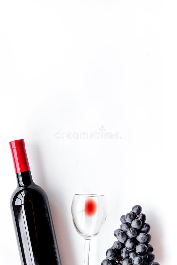 Smaak rode wijn Fles van rode wijn, glas en zwarte druif op witte hoogste mening als achtergrond copyspace royalty-vrije stock afbeelding