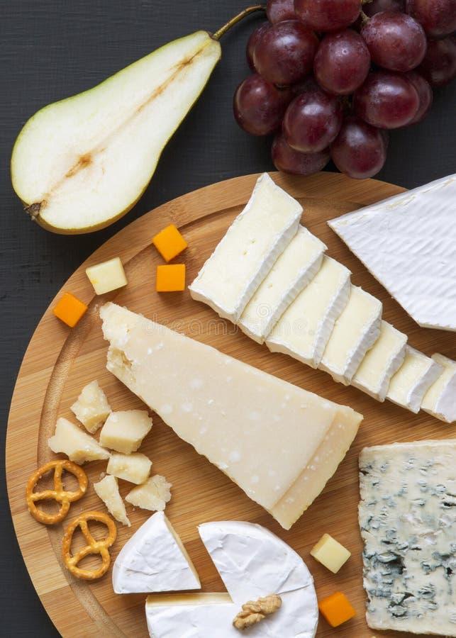 Smaczny ser z owoc, preclami i orzechami włoskimi na zmrok powierzchni, odgórny widok Jedzenie dla wina overhead fotografia stock