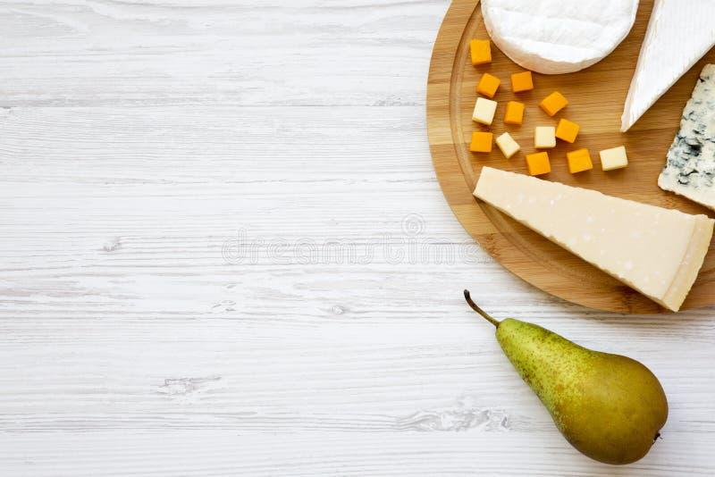 Smaka olika ostar med päronet på en vit träbakgrund fotografering för bildbyråer