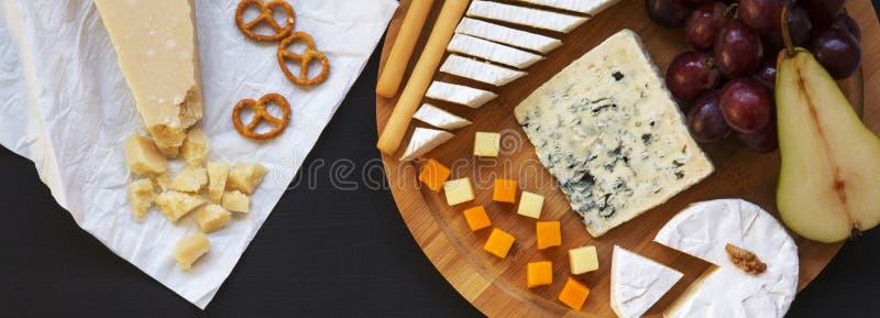 Smaka olika typer av ostar med frukter, kringlavalnötter och brödpinnar på mörk yttersida, uppe i luften Mat för vin överkant arkivfoton