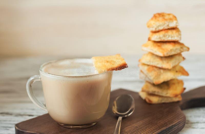 Smakelijk beeld van voedsel, een kop met geurige koffie, mocha, melk op een torentjeachtergrond van een vierkant koekje stock afbeeldingen