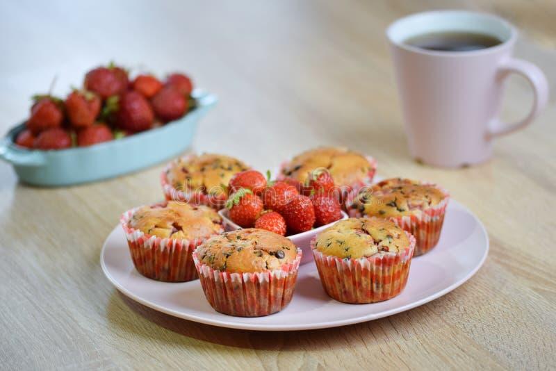 Smakelijk de zomerdessert: chocoladeschilfer en verse aardbeimuffins op een roze die plaat door verse aardbeien wordt verfraaid royalty-vrije stock foto's