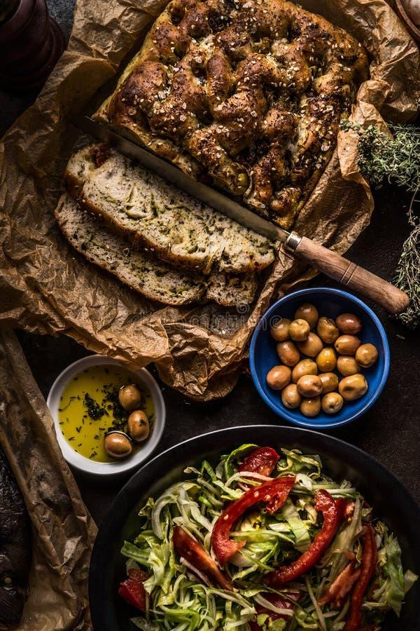 Smakelijk eigengemaakt focacciabrood op de achtergrond van de keukenlijst met verse salade, olijven en olijfolie, hoogste mening  royalty-vrije stock foto's