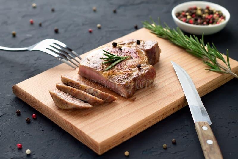 Smakelijk eigengemaakt goed uitgevoerd lapje vlees op houten scherpe raad met vork en mes op steenachtergrond stock foto's