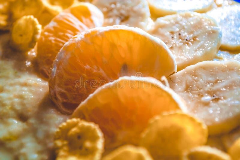 Smakelijk en nuttig ontbijt van fruit en vlokken Segmenten mandarijnen en stukken bananen Vitaminen stock afbeelding