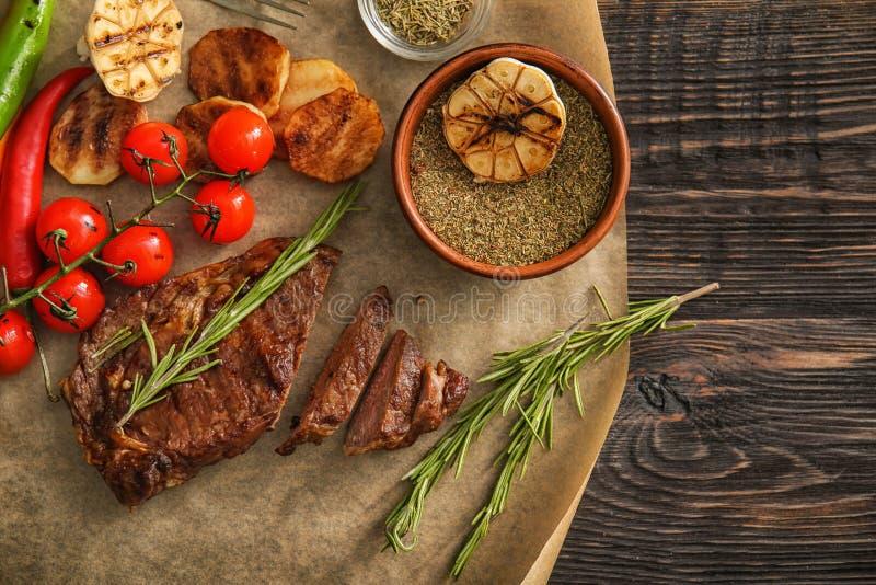 Smakelijk geroosterd vlees met groenten, kruiden en kruiden op houten lijst royalty-vrije stock foto's