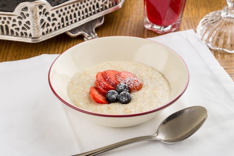 Smakelijk havermeel met fruit en bessen in kom op ontbijtachtergrond stock fotografie