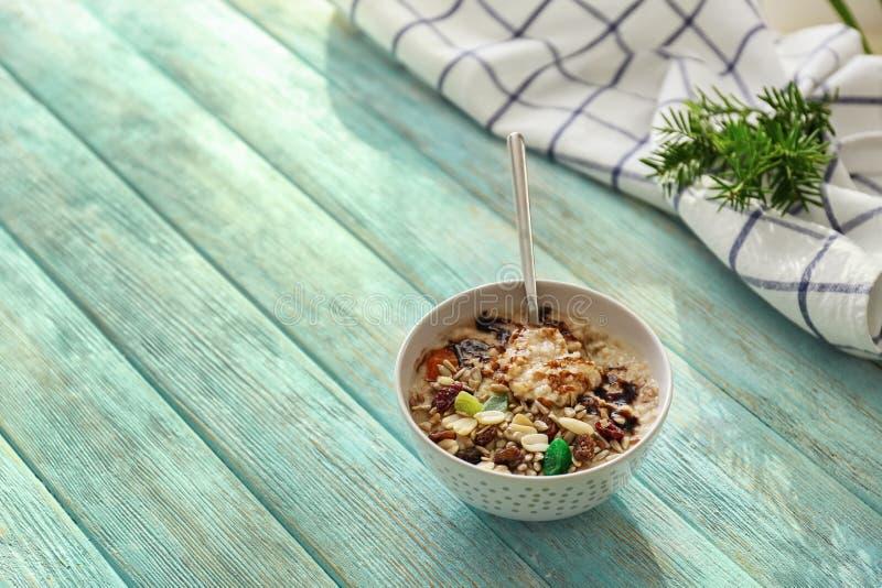 Smakelijk havermeel met noten en chocoladesaus in kom op kleuren houten lijst stock fotografie