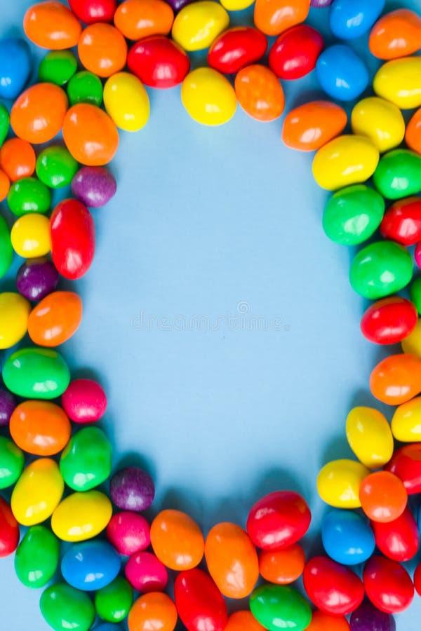 Smakelijk kleurrijk suikergoed op blauwe achtergrond Vlak leg stock afbeelding