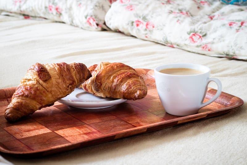 Smakelijk ontbijt aan bed Croissant met koffie stock foto's