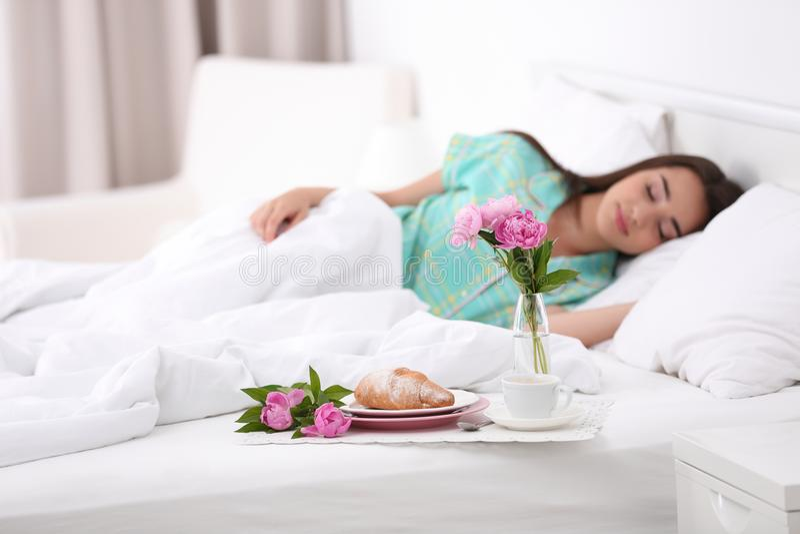 Smakelijk ontbijt en slaap jonge vrouw in bed royalty-vrije stock afbeeldingen