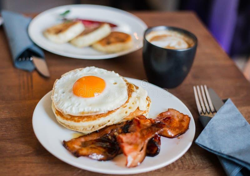 Smakelijk ontbijt met pannekoeken, gebraden ei, koffie en bacon stock afbeelding