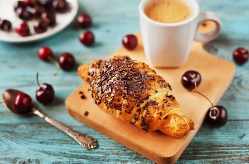 Smakelijk ontbijt met verse croissant, koffie en kersen op een houten lijst stock fotografie