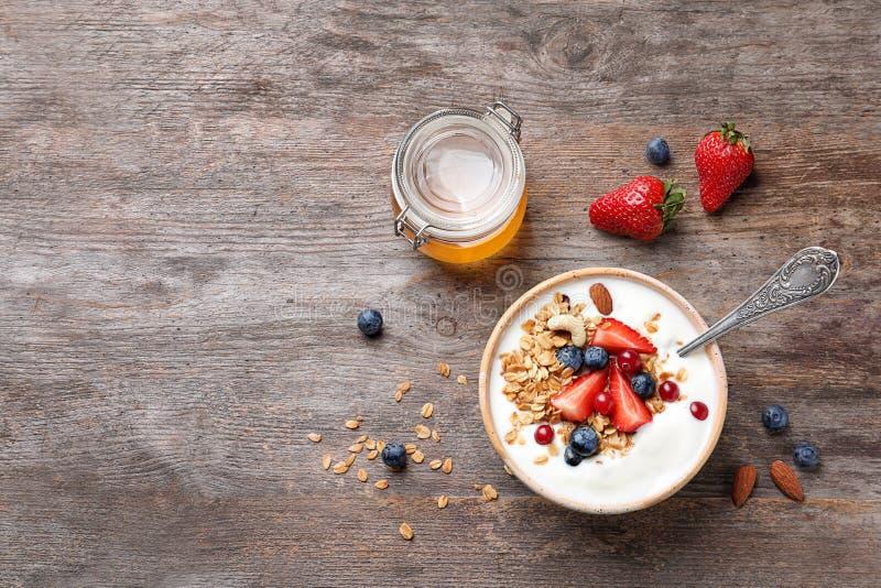 Smakelijk ontbijt met yoghurt, bessen en granola stock afbeeldingen