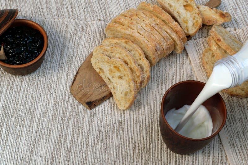 Smakelijk ontbijt Vers brood met jam en melk De melk wordt gegoten in een kop Toost met fruitjam op servet Evenwichtig voedsel ru royalty-vrije stock foto's