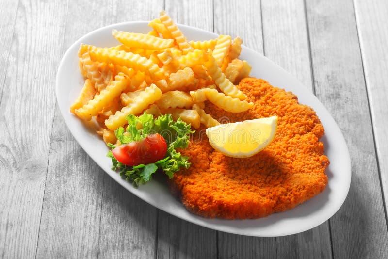 Smakelijk Recept van Afgebrokkelde Escalope met Fried Fries royalty-vrije stock afbeelding