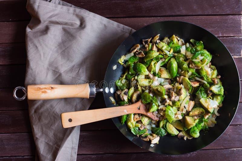 Smakelijk sauteed spruitjes en champignons in koekepan met houten keerder stock afbeeldingen