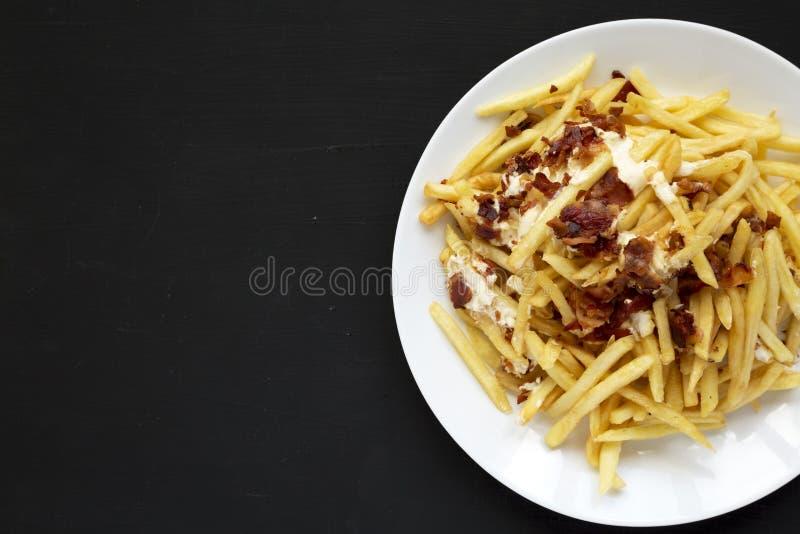 Smakelijk snel voedsel: frieten met kaassaus en bacon op een witte plaat over zwarte achtergrond Vlak leg hierboven, van, overhea stock afbeeldingen