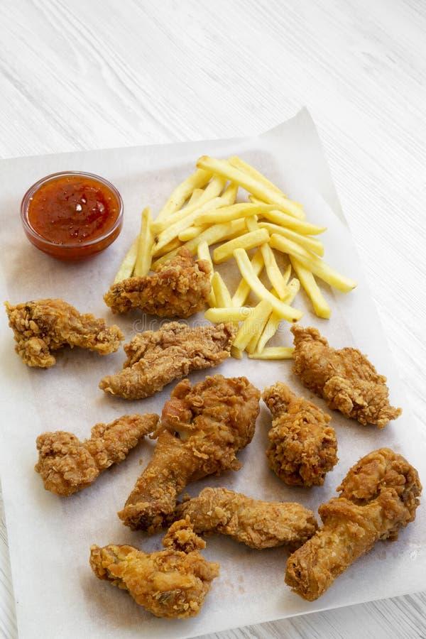 Smakelijk snel voedsel: gebraden kippenbenen, kruidige vleugels, Frieten en kippenvingers met zuur-zoete saus op bakselblad over stock afbeelding