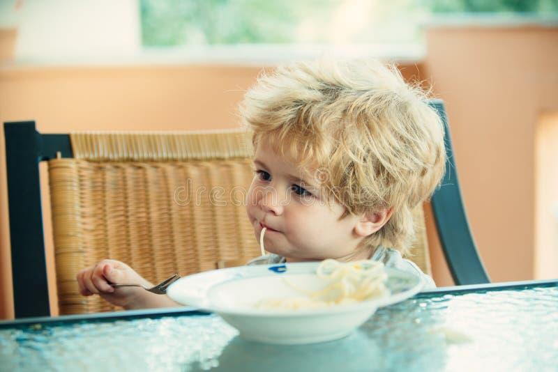 Smakelijk voedsel, leuk kind dat spaghetti eet Het kind in de keuken bij de lijst die deegwaren eten Italiaans voedsel voor kinde royalty-vrije stock afbeelding