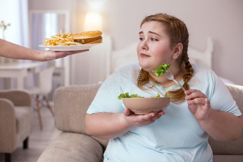 Smakelijke aantrekkelijke hamburger die mollige vrouw verleiden royalty-vrije stock foto's