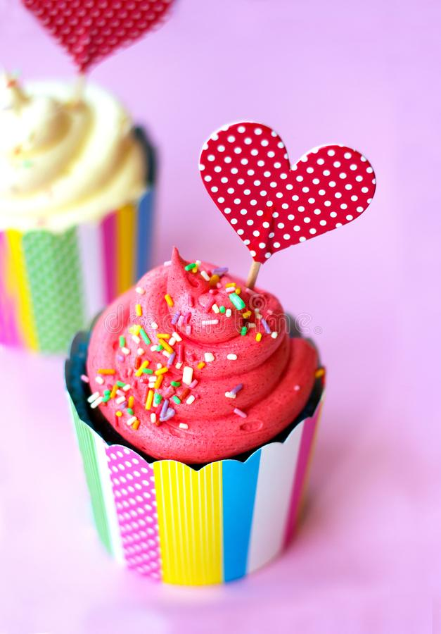 Smakelijke aardbei cupcake met rode hart topper roze achtergrond De achtergrond van de valentijnskaart royalty-vrije stock afbeelding