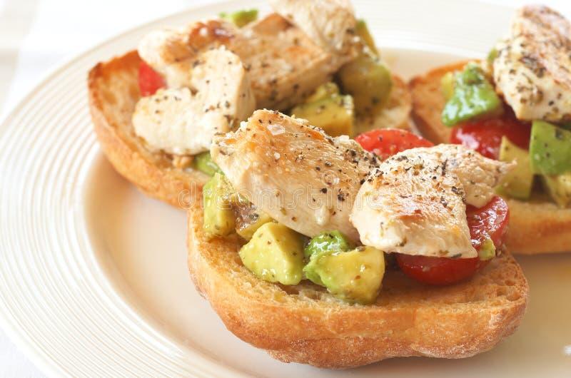 Smakelijke avocado, tomaten en kippenbruschetta stock foto's
