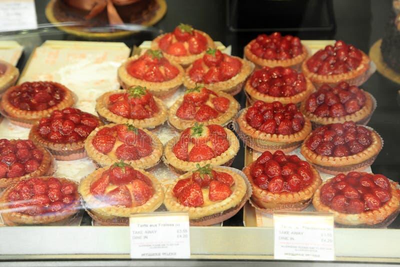 Smakelijke smakelijke banketbakkerij, aardbei scherpe pastei en rasberry scherpe pastei op een tegenshowvenster stock afbeeldingen
