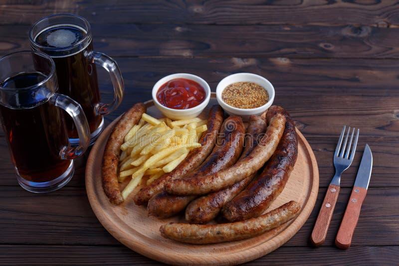 Smakelijke biersnacks Geroosterde gediende worsten en frieten royalty-vrije stock foto