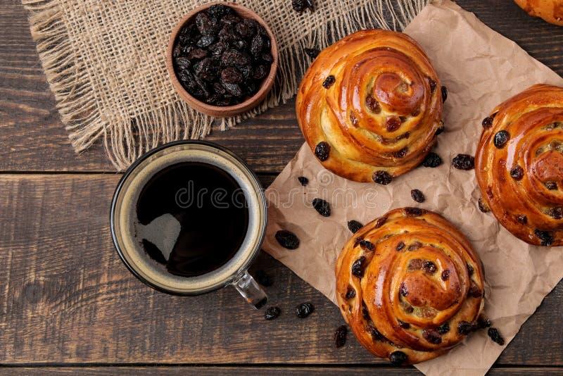 Smakelijke broodjes met rozijnen en een kop van koffie op een bruine houten lijst Verse bakkerij Het brood van het ontbijt Hoogst stock foto's