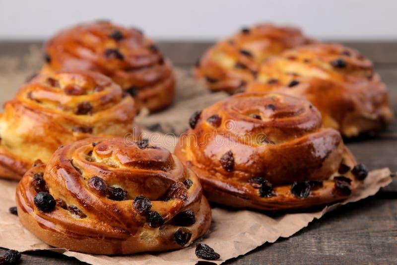 Smakelijke broodjes met rozijnen op een bruine houten lijst Verse bakkerij Het brood van het ontbijt Close-up royalty-vrije stock foto