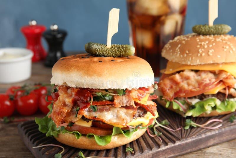 Smakelijke burgers met bacon op lijst stock fotografie