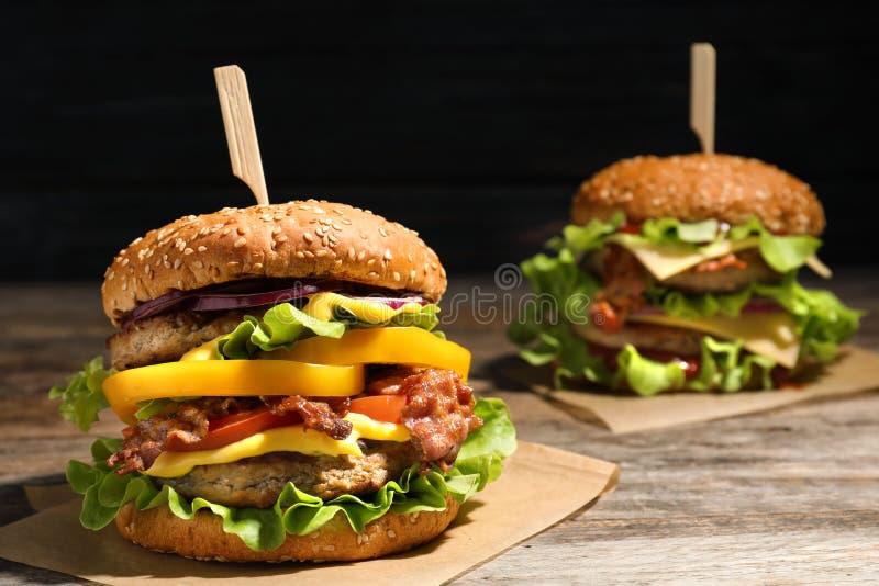 Smakelijke burgers met bacon op lijst royalty-vrije stock afbeelding