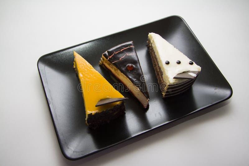 Smakelijke cakes op zwarte plaat stock fotografie