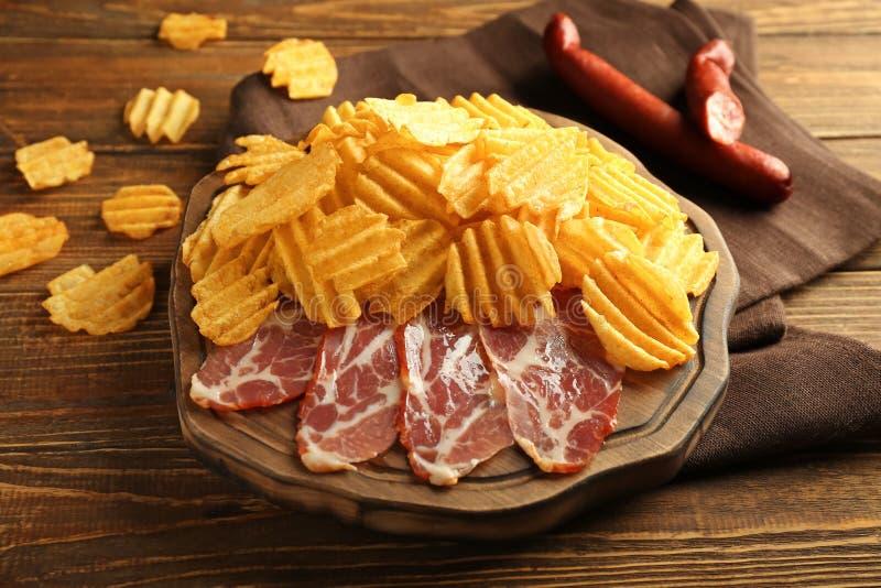 Smakelijke chips met bacon op houten raad royalty-vrije stock afbeeldingen