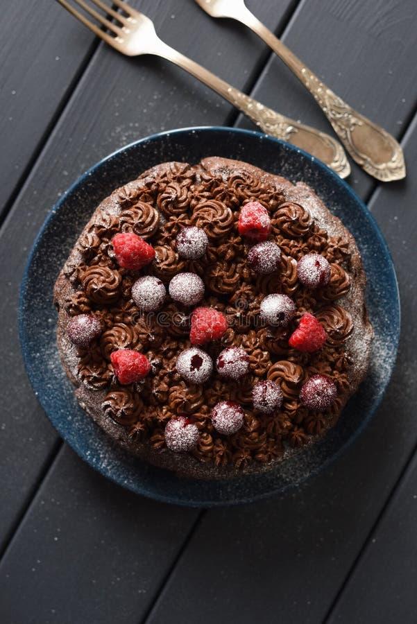 Smakelijke chocoladecake met chocoladesuikerglazuur en ruwe bessen met uitstekende vorken op donkere achtergrond stock foto's
