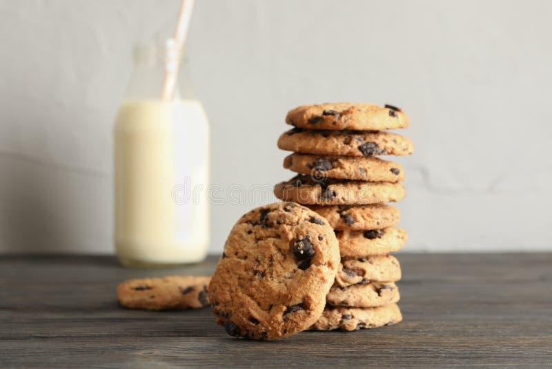 Smakelijke chocoladeschilferkoekjes en fles melk stock afbeelding