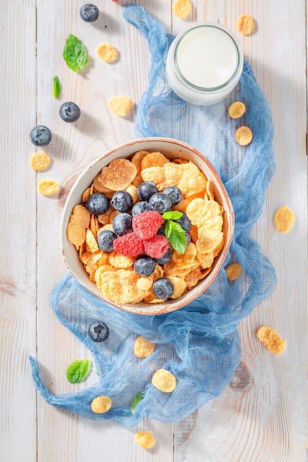 Smakelijke cornflakes met bessen en melk als gezonde maaltijd stock afbeelding