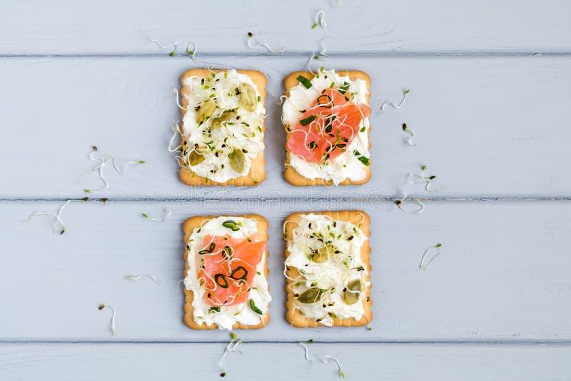 Smakelijke crackers met roomkaas, groenten, vissen Voorgerechten op grijze lijst De gezonde snacks, hoogste vlakke mening, leggen stock foto's